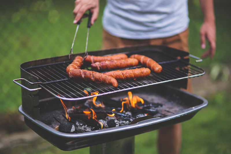 summer safety tips - man grilling hot dogs