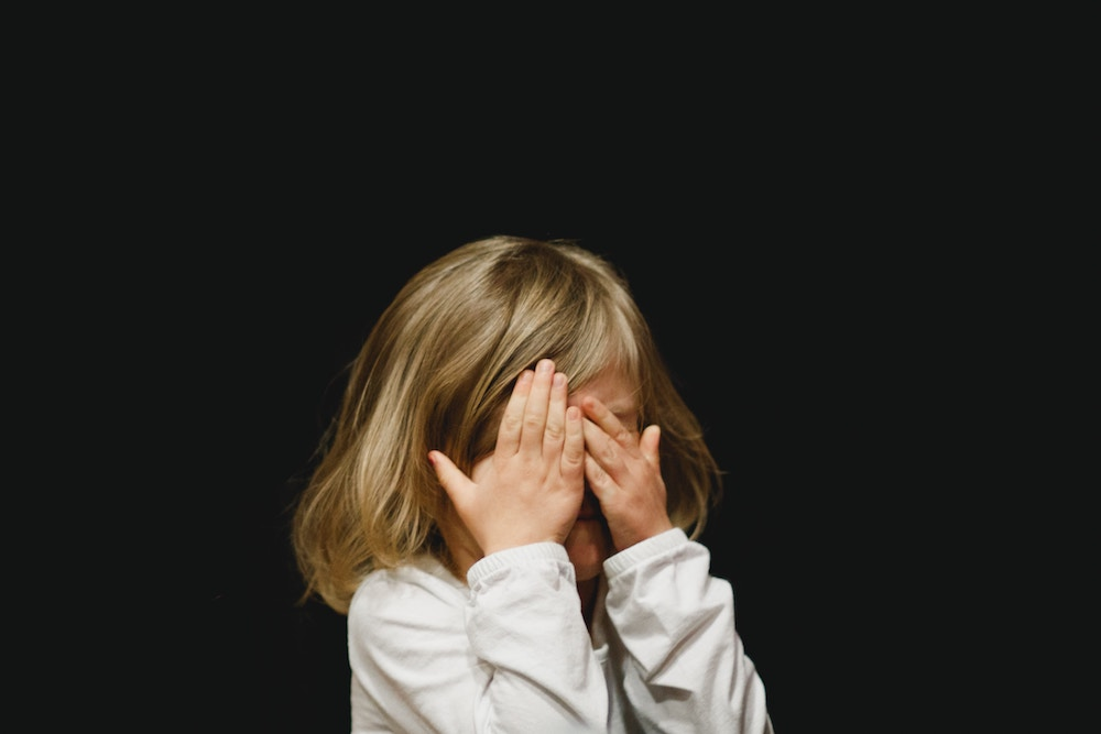 girl with hands covering face due to pink eye