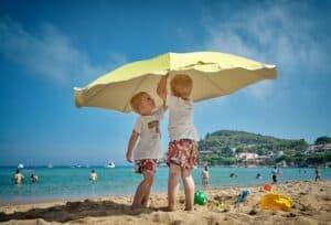 sunburn info - kids underneath umbrella on beach