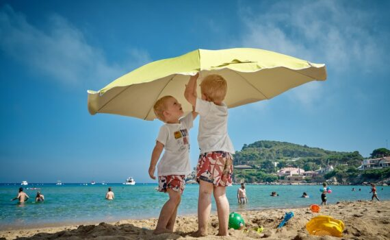 sunburn info - kids underneath umbrella on beach