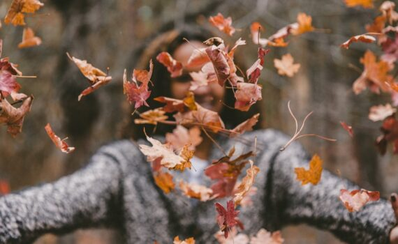 woman playing with fallen leaves - common fall health concerns