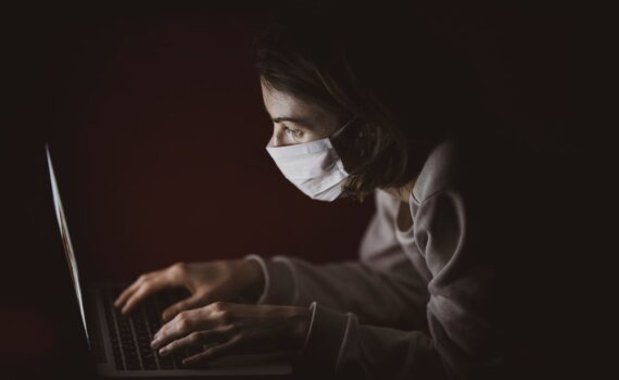 woman searching covid-19 symptoms sore throat on laptop