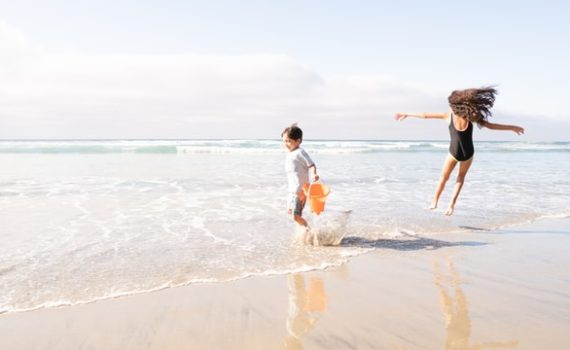 sunscreen skin protection - two children playing in water at the beach