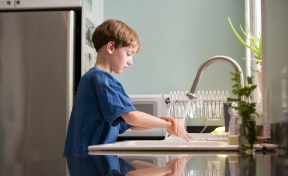 young boy washes hands to prevent respiratory illnesses